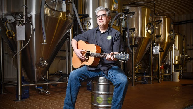 Musician and songwriter Chris Laumb plays his guitar Friday, April 1, at Beaver Island Brewing Co., where he is brewmaster.