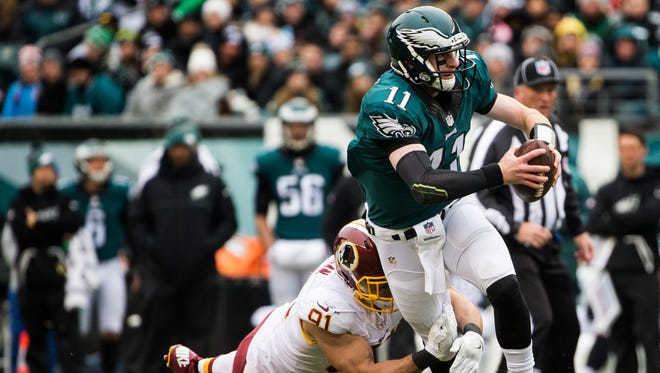 Philadelphia Eagles quarterback Carson Wentz tries to break away from Washington linebacker Ryan Kerrigan (No. 91) in the first quarter of the Eagles 27-22 loss to Washington at Lincoln Financial Field in Philadelphia, Pa. on Sunday afternoon.