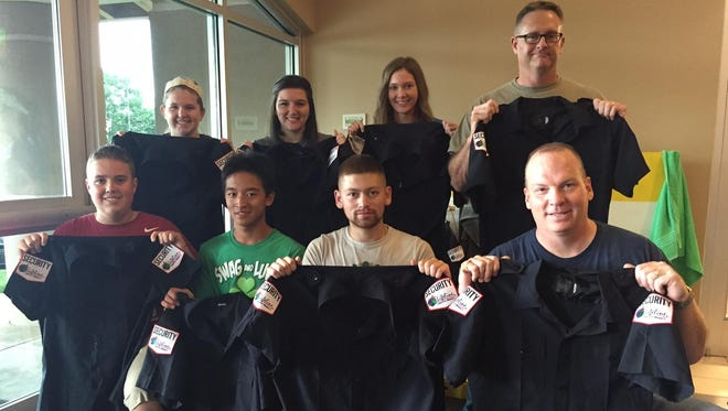 The missions team (from left, back row): Kori Evans, Nicole Pounds, Brenna Andersen, and (kneeling) Chaz Marple, Greg Holle, Cole Stokes and Springfield Police Officer James Dougherty. The team left for Haiti Monday, bring hundreds of uniforms for Haitian security guards made from used SPD uniforms.