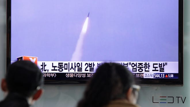 People watch a television broadcast reporting a North Korean missile launch in Seoul on March 26.