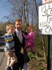 Rich Lee stands at a homemade  speed limit sign along West Asheville's  Riverview Drive with his children Curran and Arie in April.
