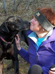 In this 2012 photo, Debby Trinen, of Sandpoint, Idaho, sits with her black Labrador retriever Joy on a late fall hike near their home. Trinen has taken Joy to a lot of veterinarians over the years, but the visits make the dog so scared she gets sick. Only recently has Trinen noticed any change, and that's because she has a fear-free vet who examines Joy on a yoga mat on the floor.