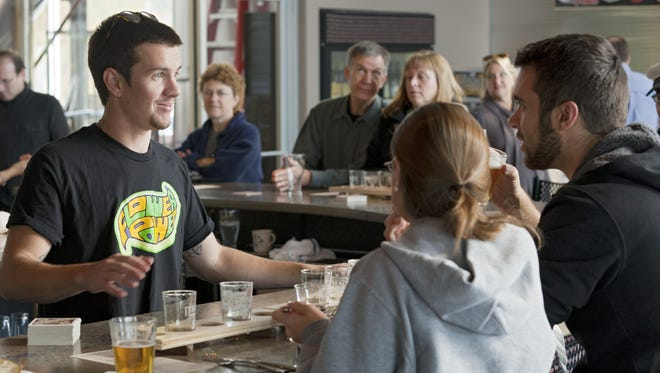 Wren Albertson-Rogers serves honeymooners Mallorie and Stephen Brown, of Franklin, Mass., in the Ithaca Beer Co.'s tasting room.