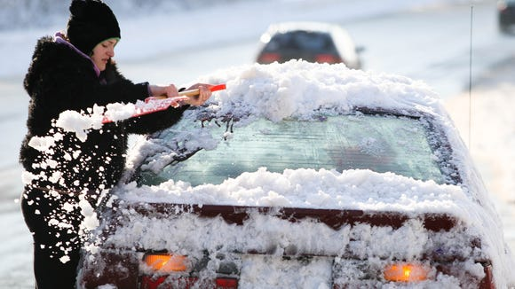 Kristine Geisler, shown here in 2011, clears snow and ice off her car along Polly Drummond Hill Road in Pike Creek.