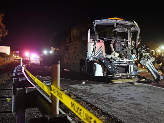 The remains of a charter bus sit in the eastbound lanes