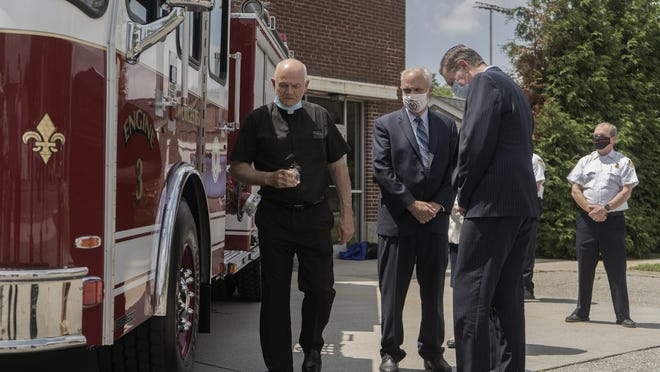 Fire Department chaplain, the Rev. Walter Riley, left, blesses a new fire engine Thursday in Worcester.
