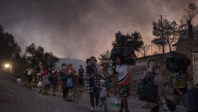 Migrants flee from the Moria refugee camp during a second fire, on the northeastern Aegean island of Lesbos, Greece, on Wednesday, Sept. 9, 2020. Fire struck again Wednesday night in Greece's notoriously overcrowded refugee camp on the island of Lesbos, a day after a blaze swept through it and left thousands in need of emergency shelter. The fires caused no injuries, but they renewed criticism of Europe's migration policy.