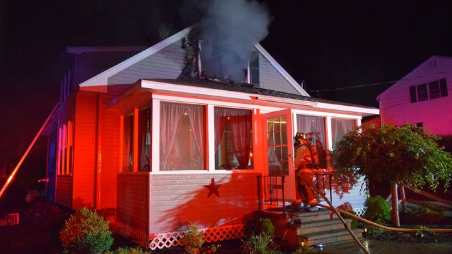 Firefighters enter a Holden house Saturday, June 13, to fight a fire.