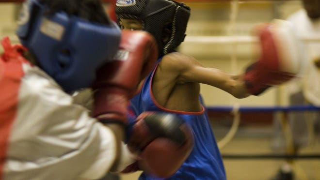 Destyne Butler Jr., 11, right, throws a punch to Kenneth Sims Jr., 12, during a sparring session at the Robert Taylor Gym on Nov. 15, 2006.