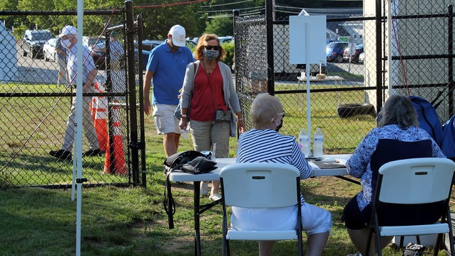 Voters check in with social distancing and face masks to conduct town business on the school baseball field in West Boylston Monday night.