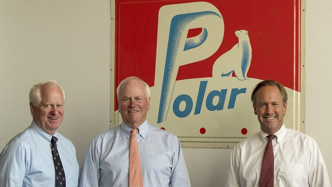Polar Beverages executive vice president & treasurer Christopher Crowley, President & CEO Ralph Crowley, and senior vice president of sales John Wetzonis, left to right, are photographed with a vintage Polar sign in the company headquarters on Southbridge Street Thursday.