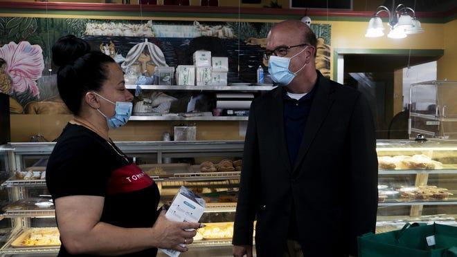 Congressman James P. McGovern hands Omayra Augosto reusable masks at Ajo y Cilantro Thursday in Worcester.