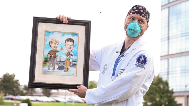 Dr. George Debusk shows off the gift that was presented to him by Dan Hall's family. Debusk, a trauma surgeon at UMass Memorial Medical Center - University Campus, helped save Hall's life after he was critically injured in a motorcycle crash in June.