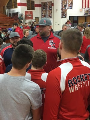 Spencer/Columbus Catholic wrestling coach Jake Zschernitz, center, addresses his team after the Rockets won a WIAA Division 2 regional title Saturday at Medford.