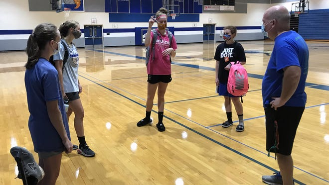 Grain Valley basketball players, from left, McKenah Sears, Ella Clyman, Grace Slaughter and Ella Quirarte have a post practice visit with coach Randy Draper following Tuesday morning's practice session in the high school gymnasium.