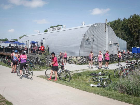 Cyclists pull into the Flat Tire Lounge in Madrid for refreshments during the Pigtails Ride on Saturday, May 19, 2018.