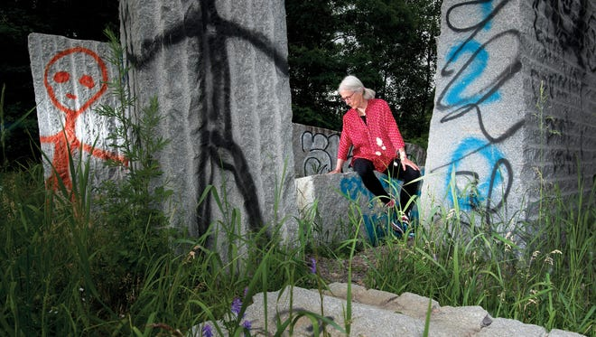 Artist Kate Pond sits inside the dismantled remains of her granite sculpture that once stood near the Moran Plant in Burlington.  Now covered in graffiti, the sculpture was moved in advance of construction at the Moran Plant.