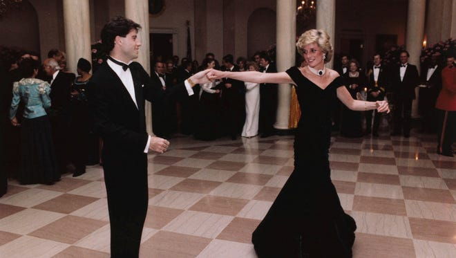 """FILE - In this Nov. 9, 1985 photo provided by the Ronald Reagan Library, actor John Travolta dances with Princess Diana at a White House dinner in Washington. This outfit is featured in an exhibition of 25 dresses and outfits worn by Diana entitled """"Diana: Her Fashion Story"""" at Kensington Palace in London, opening on Friday, Feb. 24, 2017. (Ronald Reagan Library via AP, File) ORG XMIT: LON119"""