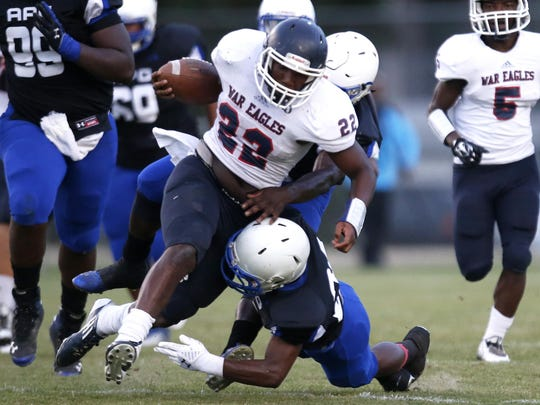 Wakulla's Monterious Loggins is brought down by Godby's B.J. Gant, bottom, and Kani Daguerre during a jamboree at Gene Cox Stadium in the spring.