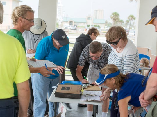 Protesters sign petitions and gather at the pavilion at Pensacola Beach Saturday, August 5, 2017 to help get the word out to stop the passage of Bill S.B 1073 during the Save Pensacola Beach Rally.