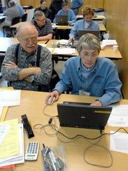 Volunteer AARP tax preparer Jackie Thiry, right, helps