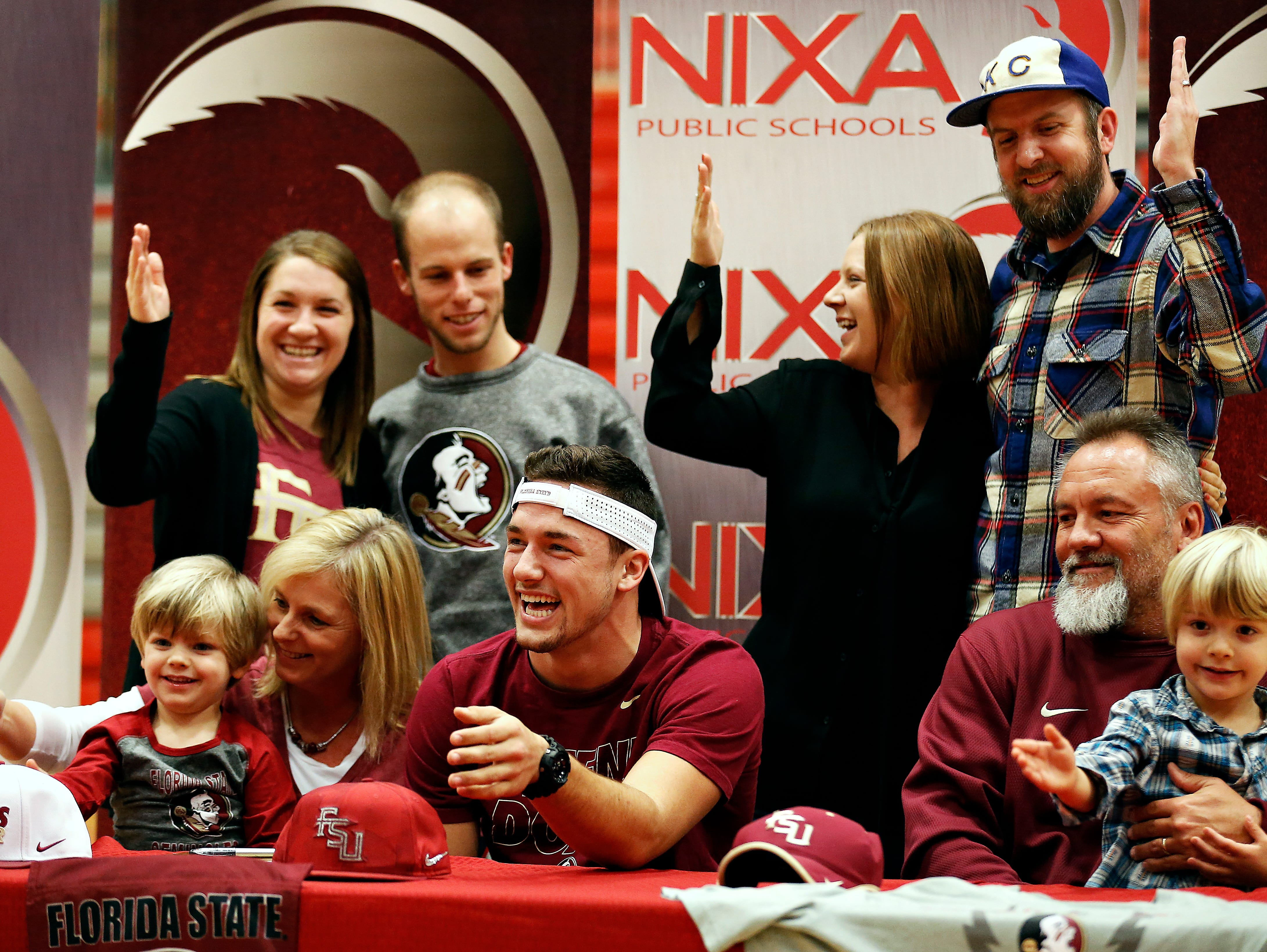 """Nixa High School senior Logan Tyler and his family do the """"Tomahawk Chop"""" after Tyler signed a national letter of intent to play football at Florida State University at the Nixa High School gym in Nixa, Mo. on Feb. 3, 2016."""