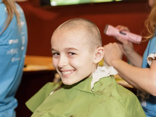 A youngster brandishes a shaved head in solidarity with kids being treated for cancer at a recent St. Baldrick's Foundation charity event at Amalfis Restaurant in Lawrenceville.
