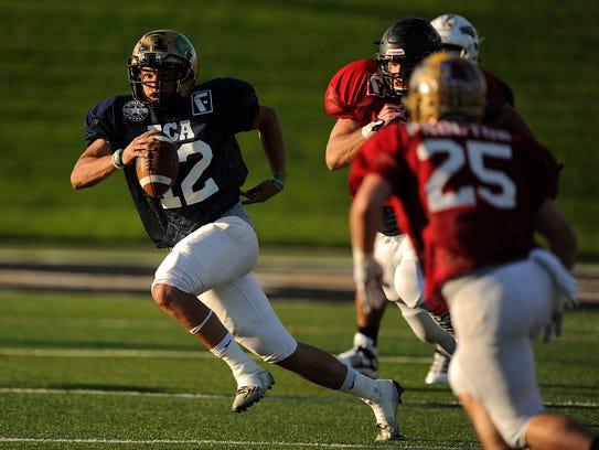 Blue team quarterback Peyton Killam (12) runs through