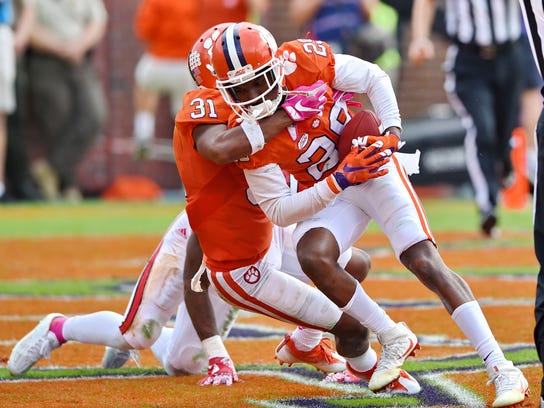 Clemson's Marcus Edmond (29) and Ryan Carter (31) celebrate Edmonds game-ending interception in overtime of an NCAA college football game against North Carolina State, Saturday, Oct. 15, 2016, in Clemson, S.C. Clemson won 24-17 in overtime. (AP Photo/Richard Shiro)