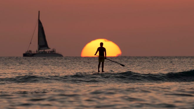 A paddleboarder looks our over the Pacific Ocean on Dec. 31, 2013, as the sun sets off of Waikiki Beach, in Honolulu. Airline mileage cards usually aren't the best way to earn a free vacation. For most fliers, a cash back credit card could be the most rewarding path.