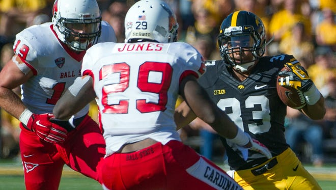Iowa Hawkeyes running back Jordan Canzeri (33) tries to avoid the tackle of Ball State's Brian Jones (29) at Kinnick Stadium.
