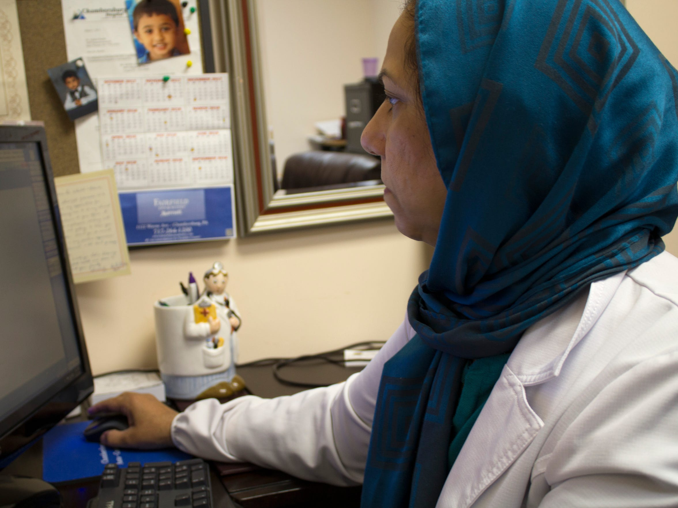 Amatul Khalid works at her desk the morning of Nov. 1 at the Chambersburg Medical Associates on Scotland Avenue. Khalid works as a doctor of internal medical, while her husband, Akram, manages the office. The two opened the practice in 2005 after they moved to the area.