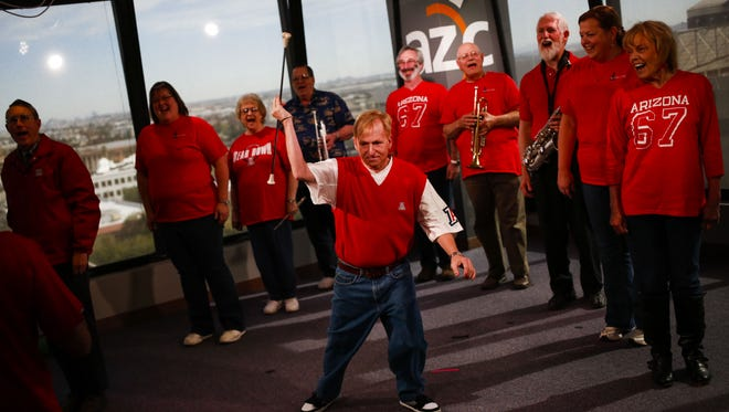 John Lee spins a baton as some members of the University of Arizona marching band who performed in the first Super Bowl rehearse for a short song in The Arizona Republic newsroom studio on Saturday, Jan. 30, 2016, in Phoenix, Ariz.