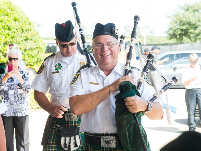 A member of the Pipes and Drums bagpipers of the Orange County Sheriff's Department smiles after a rousing performance by the band.