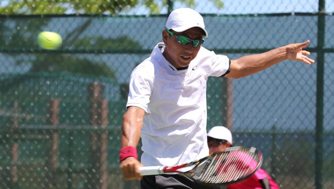 Defending champion Takao Suzuki of Japan plays a backhand against Japan's Yuichi Ito in a Round 1 match of the 2016 King's Guam Futures tennis tournament presented by Docomo Pacific and Hilton Guam Resort and Spa Tuesday at the Hilton tennis courts. Suzuki was leading 4-6, 7-6(7), 4-2 before Ito retired from the match with an injury.