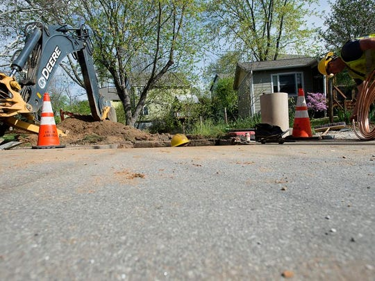A water maintenance worker peeks his head up, while Tyler White unravels piping for a water tap for a new house Thursday on Nebraska Street in West Asheville.