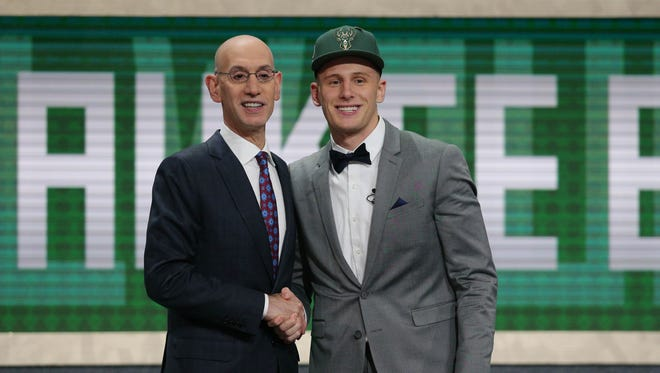 Donte Divincenzo  greets NBA commissioner Adam Silver after being selected by the Milwaukee Bucks in the NBA draft.