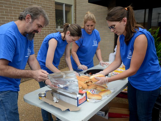 Jeff Kindrick, Mandi Forsythe, Pam Kindrick and Rachel Keymon help with preparing hot dogs Friday during Teel & Maroney's annual community cookout. The event was held to benefit Area Relief Ministries.