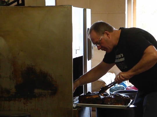 Mark Lammar takes smoked pork butts out of his smoker Thursday at Lammar's Smokehouse BBQ in Marshfield.