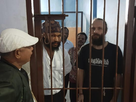 This undated photo provided by Jakub Skrzypski's legal defense team, shows the Jakub Skrzypski from Poland, right, standing inside a holding cell before a court appearance in Wamena, Papua province, Indonesia. Skrzypski, who is on trial for treason in Indonesia after meeting with Papuan independence supporters, said that visitors to his prison assaulted him and threatened to kill him as guards watched. Standing on the left is Simon Magal, the Papuan man Skrzypski had been in touch with who is also on trial. (Jakub Skrzypski's Legal Defense Team via AP)