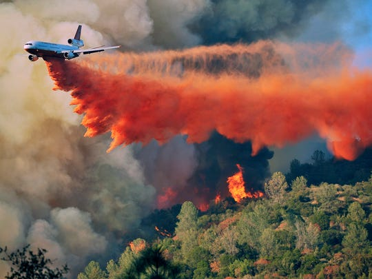 An air tanker drops fire retardant on a fire which was burning on a ridge northeast of Oakhurst on Monday. One of several wildfires burning across California prompted the evacuation of hundreds of people in a central California foothill community near Yosemite National Park, authorities said.