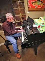 Doug Arnholter plays a little jazz piano during a First Friday art tour at R & B Architects.
