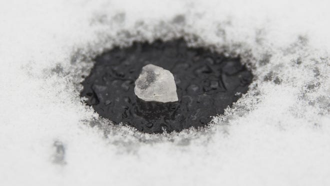 A piece of rock salt melts a small patch in the snow.