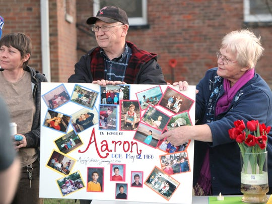Jim and Connie Berns show photos from the childhood of their adopted son, Aaron Berns, at a vigil in Morrow on Sunday.