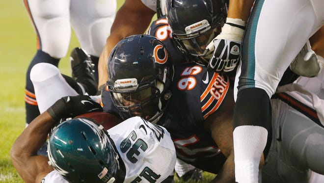 Philadelphia Eagles running back Matthew Tucker (39) rolls into the end zone for a touchdown as Chicago Bears defensive tackle Ego Ferguson (95) and defensive end Trevor Scott (76) tackle him in an NFL preseason football game Friday, Aug. 8, 2014, in Chicago.