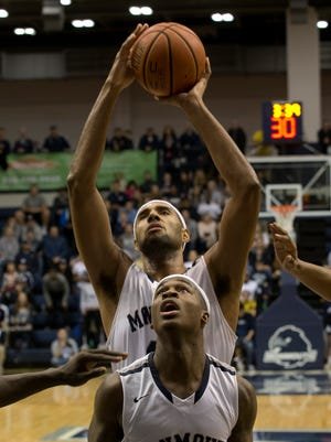Monmouth's Chris Brady goes up with a shot after pulling in a rebound. In front of him is teammate Josh James. Monmouth University basketball vs Quinnipiac in West Long Branch, NJ on January 9, 2016.