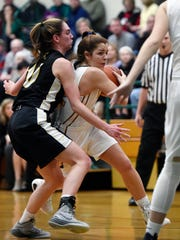 York Catholic's Kate Bauhof drives against Delone Catholic's Maddie Clabaugh in the first half of a YAIAA girls' basketball game Wednesday, Jan. 4, 2017, at York Catholic. After earning its first lead over Delone Catholic late in the fourth quarter, York Catholic won 67-62.