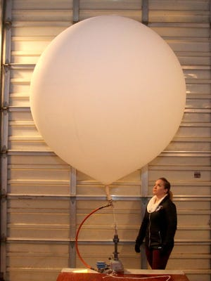 Sara Schultz watches a weather balloon fill up with hydrogen before its launch at the top of a hill on the grounds of the National Weather Service in White Lake. Balloons get launched every day at 6 a.m. and 6 p.m.