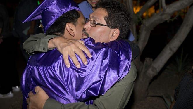 Alfonso Calderon hugs his son Gerardo Calderon after graduation from Bioscience High School in Phoenix in 2013.