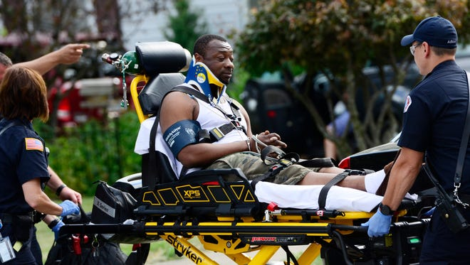 Darelle Jones, driver of a Dodge Durango that crashed into a house on North Street is transported to the hospital on Wednesday evening.